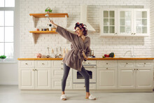 Happy Housewife Having Fun While Making Breakfast. Beautiful Young Woman In Hair Curlers, Bathrobe, Leggings And House Slippers Holding Cooking Utensils, Dancing And Singing Songs In Spacious Kitchen