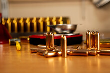 Heavy Bullets Lie On The Table In Bulk, In The Background There Are Casings In A Wooden Stand And Scales, Preparation For Reloading Cartridges, Necessary Accessories For Reloading, Soft Focus.