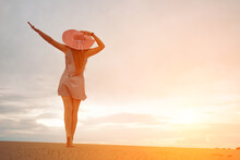 Silhouette Of A Romantic And Dreaming Young Woman Walking Down The Slope Of A Sand Dune With Her Hands Up. Female Silhouette In A Hat And Short Dress Against The Backdrop Of The Sunset Sky. Copy Space