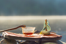 A Cup Of Tea, A Statuette Of A Buddha Stand On A Tourist Foam, In The Background Soaring Water.