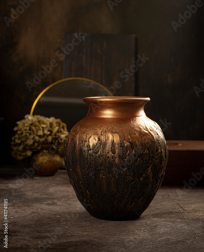 Fotografiet Copper ceramic vase in a dark interior. Handmade