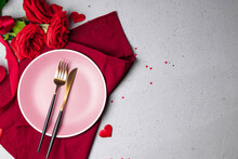 Plate, Cutlery And Red Roses On The Gray Background, Romantic Dinner Concept. Free Space For Text