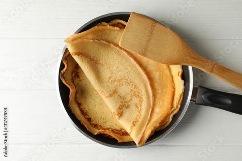 Fototapeta Pan with tasty thin pancakes and spatula on wooden table obraz