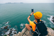 Woman Hiker Taking Photo With Smartphone On Seaside Cliff Edge