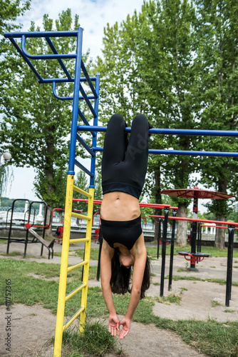 Fototapeta Young woman doing street workout on the horizontal bar, in summer morning obraz