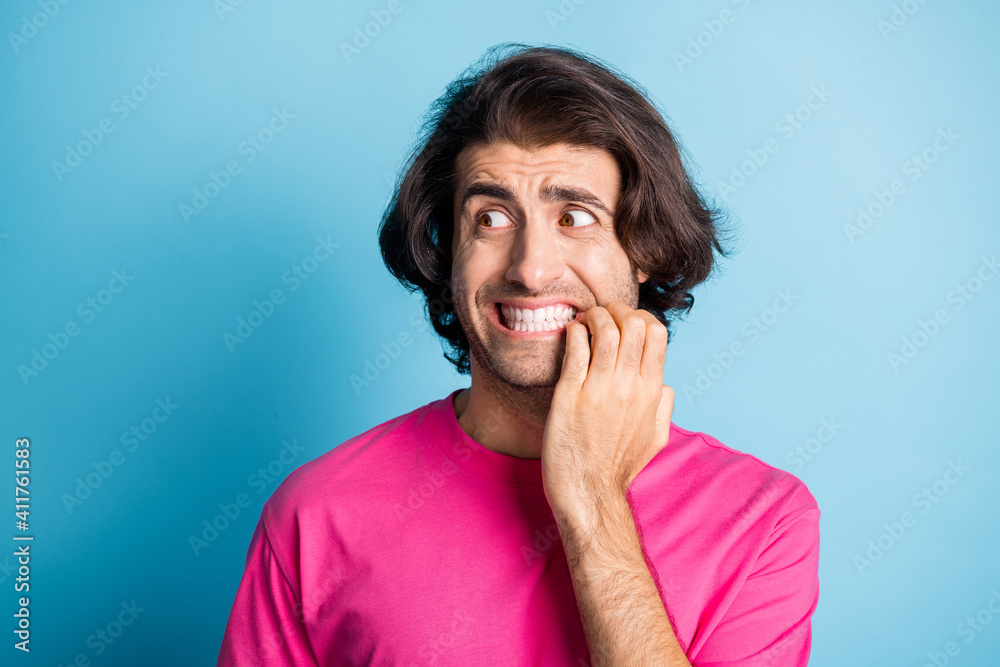 Fototapeta Photo of scared brunet hair eastern guy hold fingers mouth look empty space wear casual cloth isolated on blue background