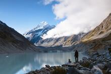 Hiker Near Glacial Lake Looking At Mt Cook At Sunset, New Zealand