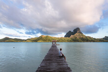Man Enjoying Sunrise On A Jetty, Bora Bora, French Polynesia