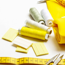 The Trendy Color Of 2021. Tailoring Concept. Beautiful Yellow Fabric With Sewing Thread, Scissors, Tape Measure, Chalk And Spool On A White Background. Top View. Flat Lay.