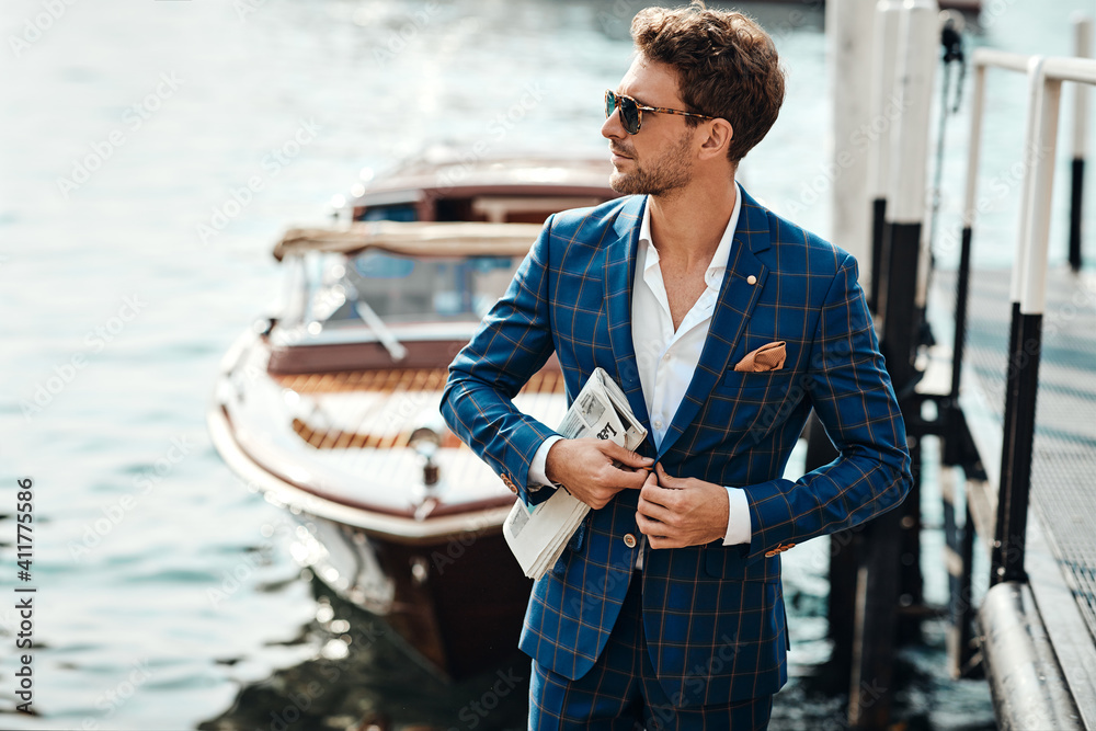 Fototapeta Young handsome man in classic suit over the blurred lake buttoning his jacket