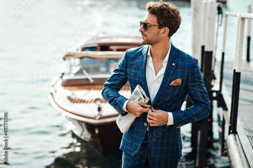 Obraz Young handsome man in classic suit over the blurred lake buttoning his jacket - fototapety do salonu