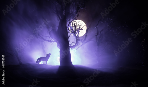 Fototapeta Silhouette of howling wolf against dead forest skyline and full moon. Creative artwork decoration. obraz