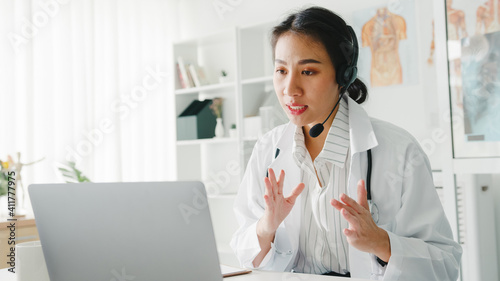 Obraz Young Asia lady doctor in white medical uniform with stethoscope using computer laptop talking video conference call with patient at desk in health clinic or hospital. Consulting and therapy concept. - fototapety do salonu