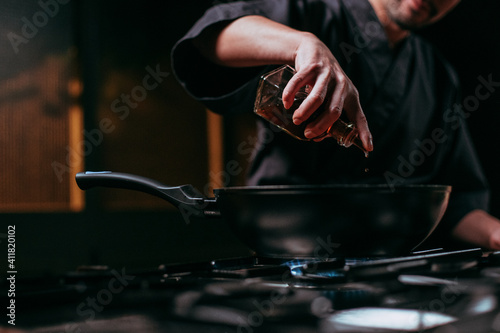 Canvas Print unrecognizable chef pouring oil into frying pan