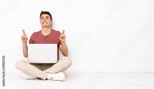 Valokuva Teenager man sitting on the flor with his laptop with fingers crossing and wishi