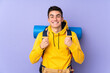 Teenager caucasian mountaineer man with a big backpack isolated on purple background celebrating a victory