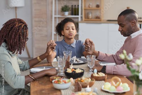 Fototapeta Portrait of modern African-American family saying grace at dinner table on Easte
