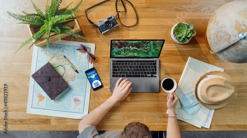 Obraz Top view of young man with laptop planning vacation trip holiday, desktop travel covid-19 concept - fototapety do salonu