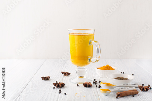Photo Golden turmeric latte in glass, spices and cinnamon on white wooden background