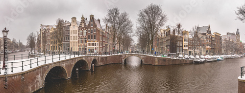 Slika na platnu Winter snow view of Dutch canal and old houses in the historic city of Amsterdam