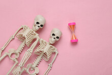 Skeletons And Hourglass On Pink Pastel Background. Time Passage Concept