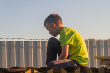 A Sad Boy Sits On The Roof Of A Barn Near A Fence With Barbed Wire In The Summer