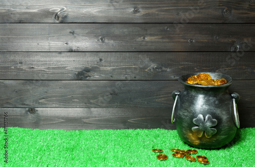 St. Patricks Day banner, poster, invitation template. Cast iron pot with four-petal lucky shamrock leaf, full of leprechaun gold coins, coins on green grass, dark wooden planks background