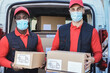 Multiracial workers delivering boxes while wearing safety masks during coronavirus outbreak - Focus on faces