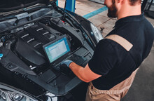 Mechanic Using Diagnostic Machine Tools Ready To Be Used With Car.