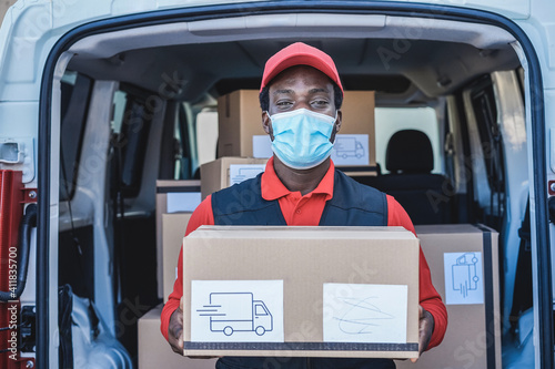 Black courier man delivering package in front of cargo truck wearing safety mask - Focus on face