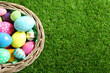 Wicker basket with Easter eggs on green grass, top view. Space for text