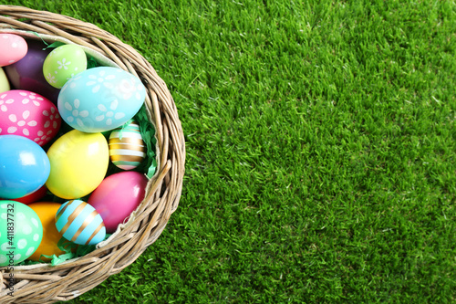Fotografija Wicker basket with Easter eggs on green grass, top view