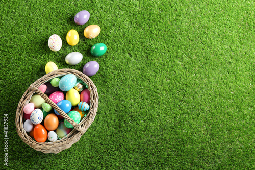 Obraz na płótnie Wicker basket with Easter eggs on green grass, flat lay