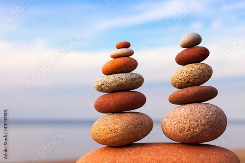 Obraz Two Rock zen pyramids of colorful pebbles on a beach on the background of the sea. - fototapety do salonu
