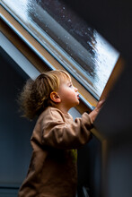 Little Preschool Boy Staying Home In Bad Weather And Looking  With Interest Through Window On Raindrops And Hail, Idoors.