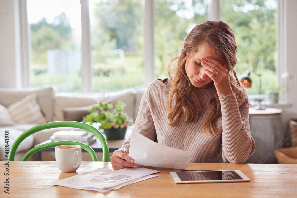 Fototapeta Worried Woman With Digital Tablet Sitting At Table At Home Reviewing Domestic Finances