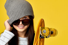 Portrait Of Little Child Girl In Gray Hat And Sunglasses Posing With Yellow Skateboard On Yellow Background, Close-up