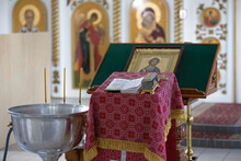 The Interior Of A Christian Church. Prayer Table Covered With Patterned Red Cloth. A Metal Container With Holy Water For Baptism. Bible, Casket, Icon And Blurred Iconostasis In The Background.