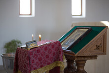 The Interior Of A Christian Church, A Prayer Table With A Bible And An Altar With An Icon. Sunlight From The Windows In The Background.