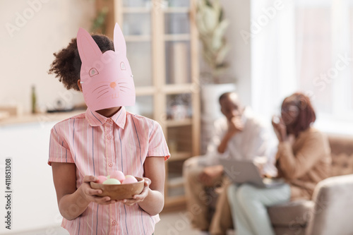 Obraz Waist up portrait of African-American girl holding Easter eggs and wearing Bunny mask while enjoying Spring holidays, copy space - fototapety do salonu