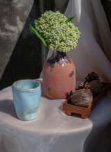 Blue Ceramic Mug Handmade With Bunch Of Flowers In Vase And Dried Cerbera Oddloam's On White Table In Vintage Room With Old Ruins Cement Wall. Selective Focus.