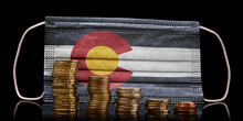 Medical Mask With The Flag Of Colorado Behind Some Shrinking Stacks Of Various Coins.(series)