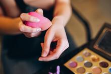 Close-up Of A Pink Beauty Blender In Hand. Beauty Blender Picks Up Concealer