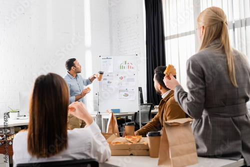 Indian businessman with pizza and coffee to go standing near flipchart and colleagues on blurred foreground