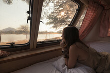 Young Asian Woman Relaxing And Looking The View In Motor Home On Campsite At Evening