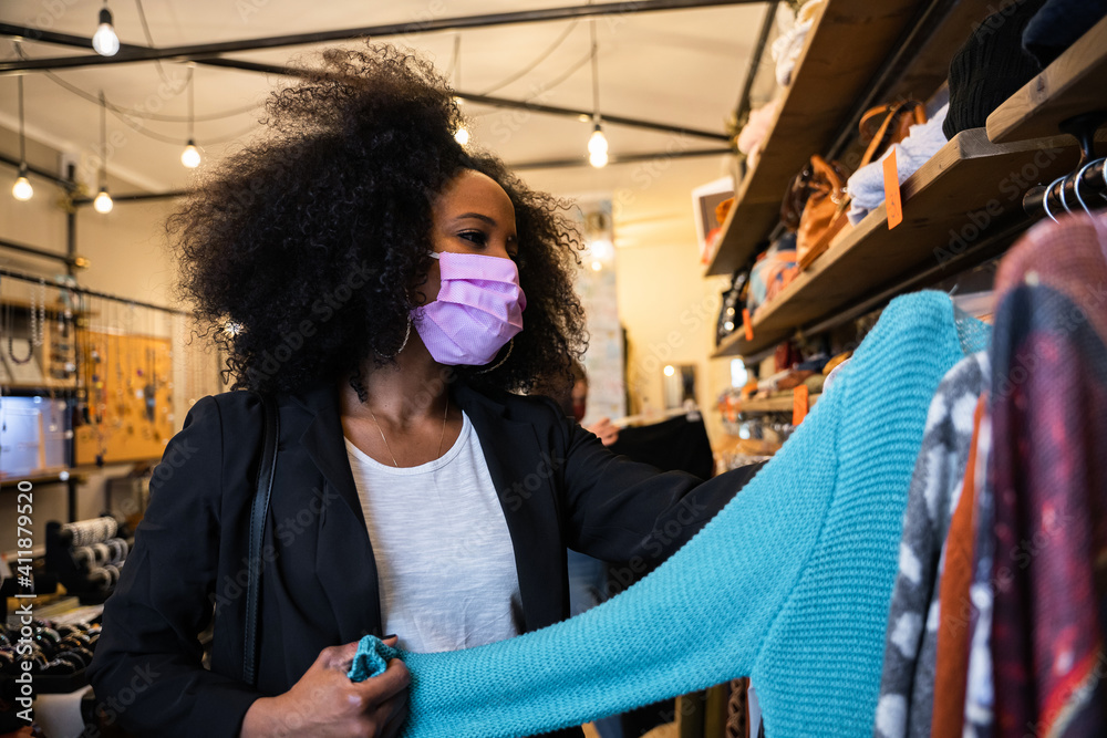 Fototapeta Portrait of a customer in a clothing store looking at a sweater for sale - Millennial woman wearing protective masks against Coronavirus infection, Covid-19 - Modern and fashion store