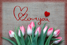 Pink Tulips And Two Red Hearts Isolated On A Cloth Background.