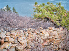 Old Stone Fence At Foothills Of Rocky Mountains Above Horsetooth Reservoir - A Popular Recreational Area In Northern Colorado, Fall Or Winter Scenery With A Low Water Level