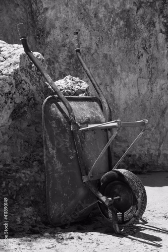 Fotografia Abandoned Wheelbarrow Against Rock
