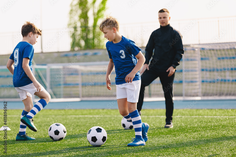 Fototapeta Boys Training Soccer Outdoor Witch School Coach on Summer Sunny Day. Happy Kids Running Classic Football Balls on Grass Training Field
